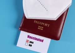 Mask on passport Vaccination card on blue background
