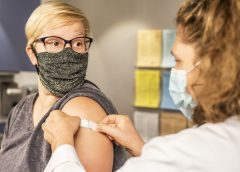 a health care provider places a bandage on the injection site of a patient, who just received a vaccine