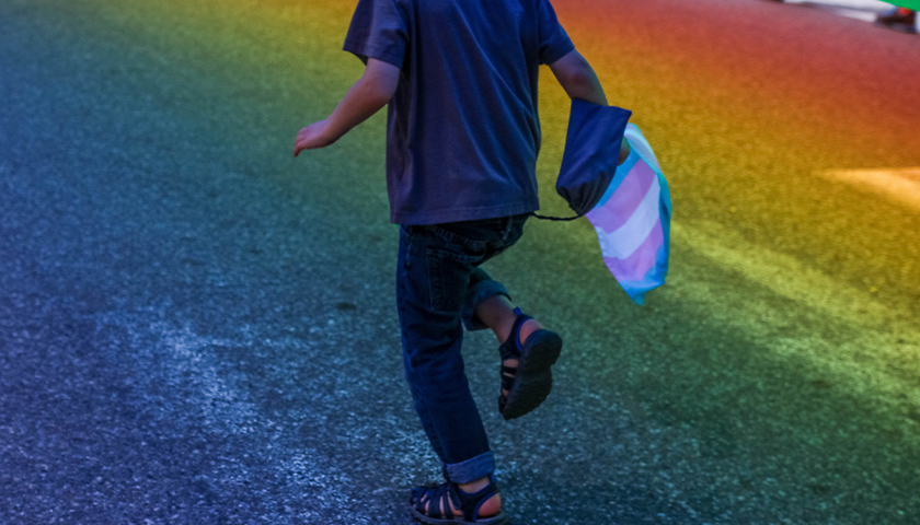 child running with trans flag