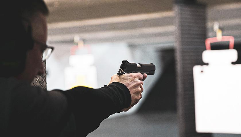 Person shooting a hand gun in a shooting range