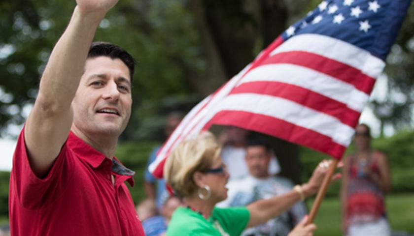 Paul Ryan wearing a red shirt and waving