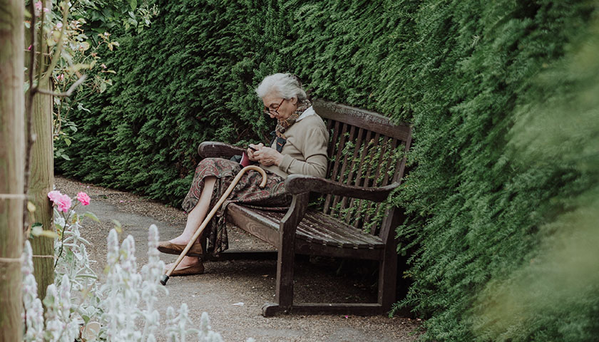 Old woman sitting on brown bench