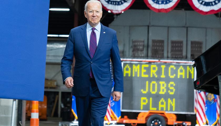 "Joe Biden walking with ""American Jobs Plan"" sign"