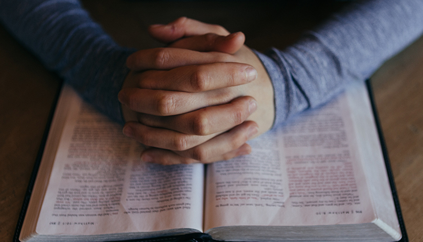 Hands praying on top of a Bible